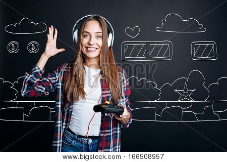 Spend time with pleasure. Joyful smiling young woman wearing headphones and holding game console while playing video games