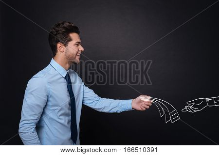 Pleasant transactions. Handsome delighted young man smiling and handing over papers to someone while standing against isolated black background.