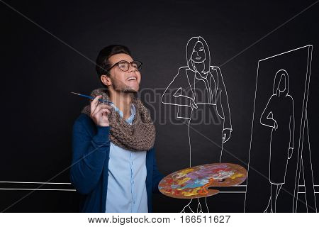 Feeling inspired. Joyful delighted young male artist holding a palette and painting a woman while standing against isolated black background.