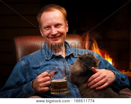 Happy man in front of the fireplace. Mug with beer favorite cat . Bliss