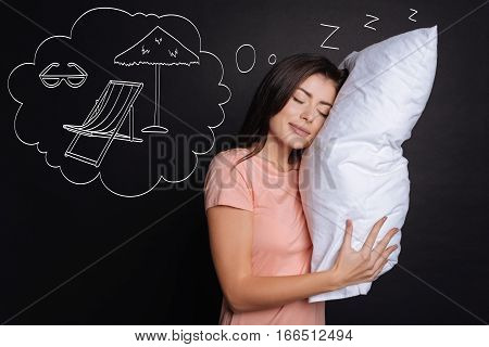 Time for dreams. Pleasant delighted woman holding pillow and dreaming about vacation while sleeping