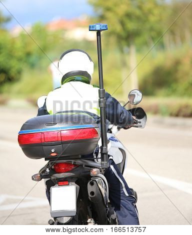 Policeman With Helmet On The Police Motorcycle While Patrolling