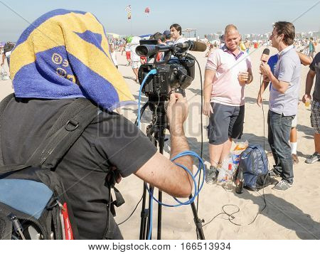 RIO DE JANEIRO BRAZIL - 25 JUNE 2014: A camera operator shields himself from the heat of the midday sun as he films a TV interview on a beach in Rio de Janeiro Brazil.