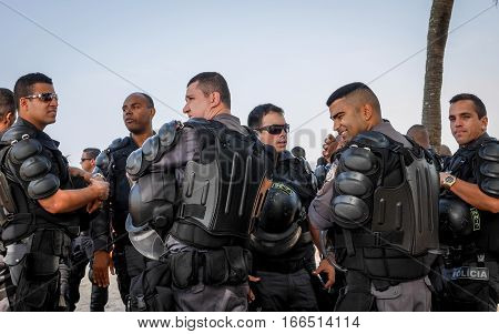 RIO DE JANEIRO BRAZIL - 28 JUNE 2016: A group of Brazilian riot police in their protective armour on patrol on Ipanema Beach.