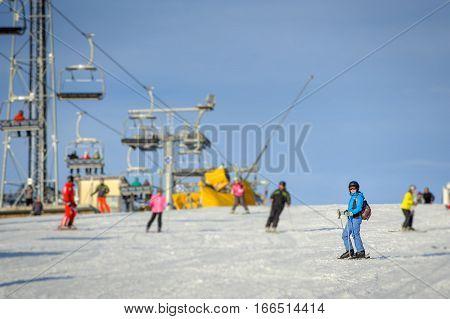 Female Skier Skiing Downhill At Ski Resort