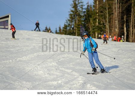 Female Skier Skiing Downhill At Ski Resort