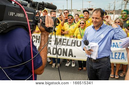 FORTALEZA BRAZIL - 4 JULY 2016: A TV interviewer prepares for broadcast outside the football stadium in Fortaleza Brazil backed by supporters of the national team.