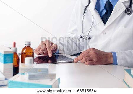 Male Doctor's Hands With Stethoscope At Desk Using Digital Tablet