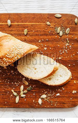 Fresh bread slices on cutting board flat lay. Top view on kitchen wood with cut crusty loaf of bread. Food, dining, dieting concept