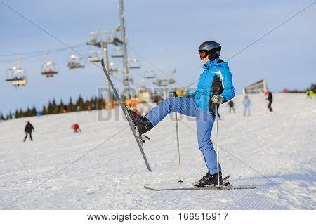 Woman Skier Skiing Downhill At Ski Resort Against Ski-lift