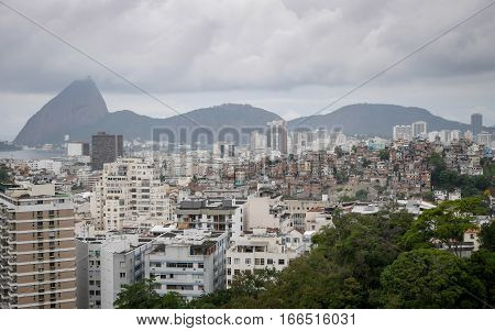 A high view over the crowded rooftops of Rio de Janeiro Brazil with more affluent apartment blocks closer to the sea and favelas perched on the hight ground.