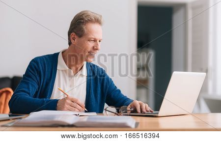 At the office. Pleasant positive grey haired man looking at the screen and making notes while working on the laptop