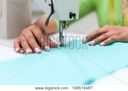 Tailoring Process - Women's hands behind her sewing machine tailor stock photo