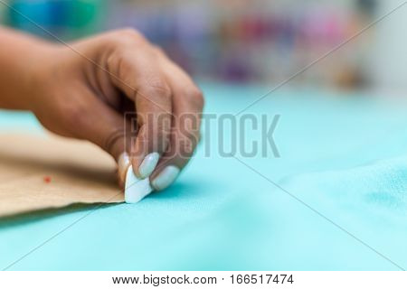 Closeup of Women fashion designer's hands marking with chalk on cloth in workshop stock photo