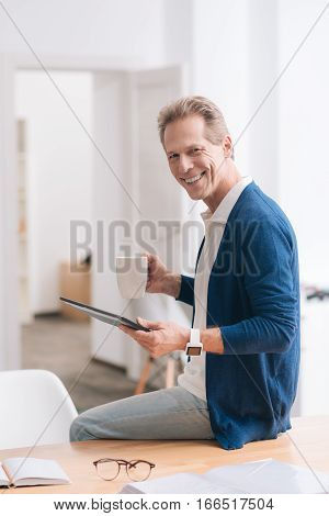 Knowing the time. Joyful nice happy man wearing the watch and holding a tablet while having tea