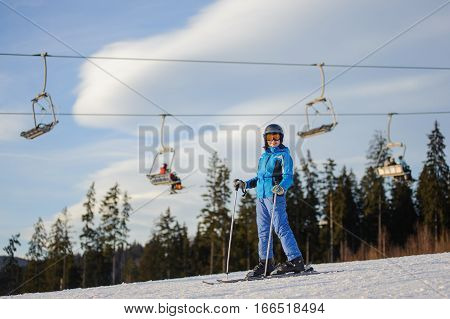 Female Skier Against Ski-lift And Forest On A Sunny Day