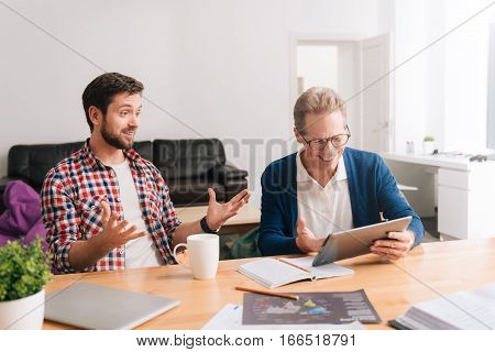 Pleasant job. Handsome joyful grey haired man looking at the tablet screen and smiling while sitting together with his colleague at the table