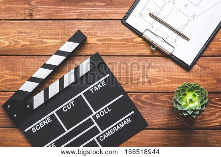 Screenwriter desktop with movie clapper board on wooden background top view
