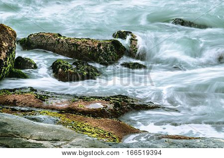 Long Exposure Photo Of Sea Water Running Over The Rocks