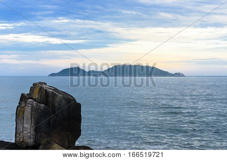 Large Vertical Stone On The Left And A Island On Background