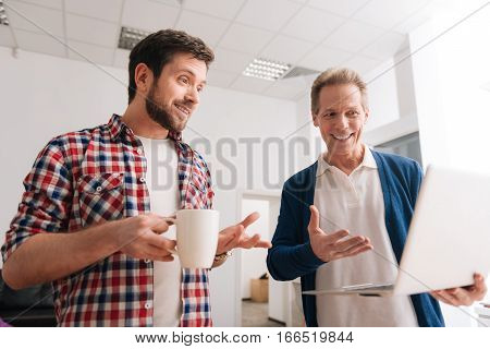 What do you think about this. Handsome cheerful pleasant man holding a laptop and showing something on it to his colleague while asking his opinion