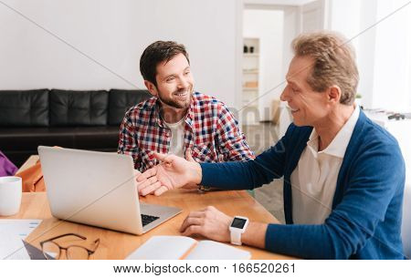 Sharing experience. Joyful pleasant grey haired man pointing with his hand at the laptop and smiling while explaining something to his younger colleague.