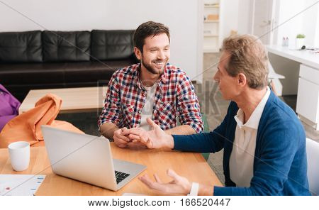Interesting conversation. Positive nice bearded man listening to his colleague and smiling while having a conversation with him