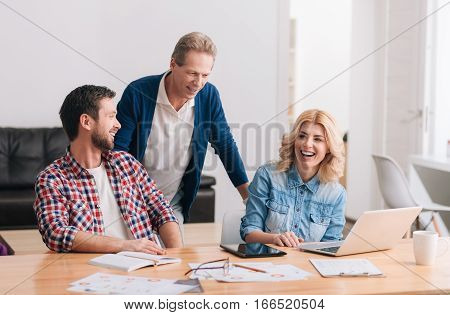 Working environment. Handsome nice positive man standing behind his colleagues and leaning forward while working with them