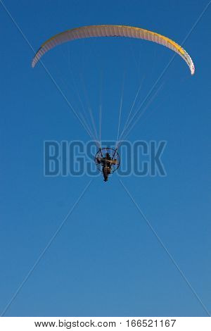 para glider with engine on his back flying in the blue sky