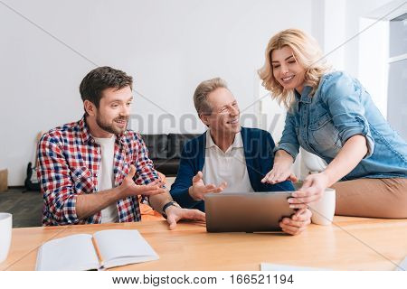 I want to show you something. Beautiful cheerful young woman sitting on the table and holding a laptop while showing something on it to her male colleagues