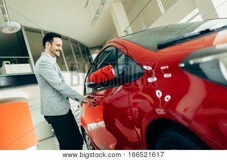 Handsome young customer buying car at dealership