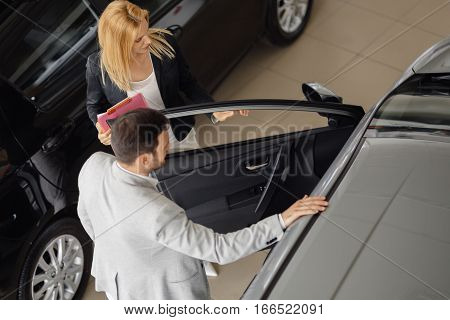 Smart salesperson selling cars at car dealership