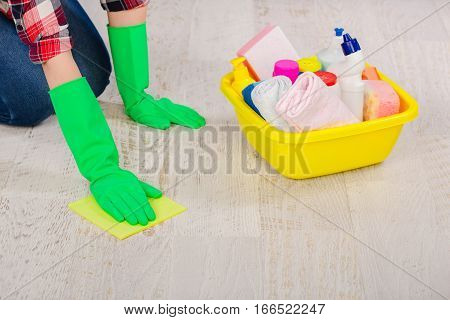 Janitor female hands dressed in protective gloves cleaning and polishing parquet floor , close-up. Professional cleaning home