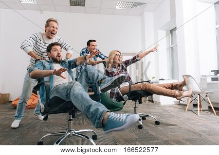 Office chair riding. Joyful happy delighted people sitting in the office chairs and having fun while riding in them