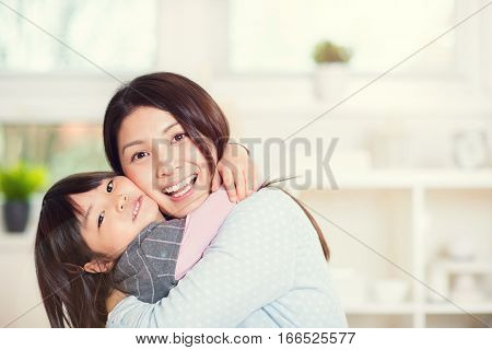 Portrait of happy japanese mother hugging with her cute little daughter at home