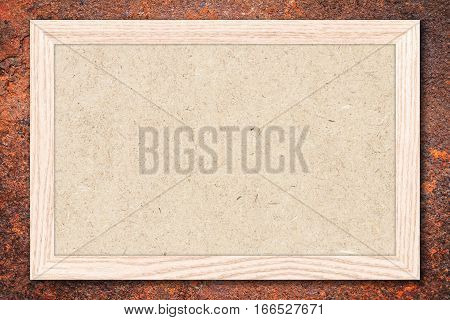 Chipboard or Empty bulletin board with a wooden frame on rusty metal background with copy space for text or image.