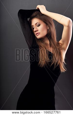 Sexy Slim Model Posing In Black Dress On Dark Grey Background And Looking Sexy With Arms Above The H