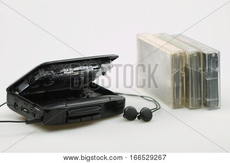 open cassette player with earphones and audio tapes
