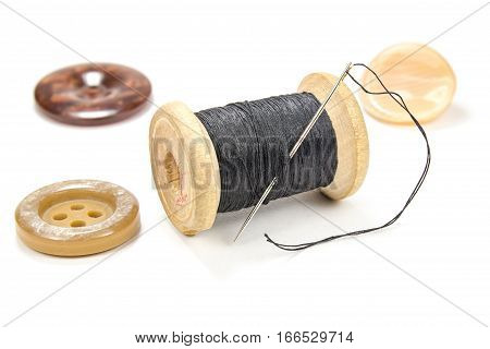 Vintage wooden spool of black thread needle and buttons on white background