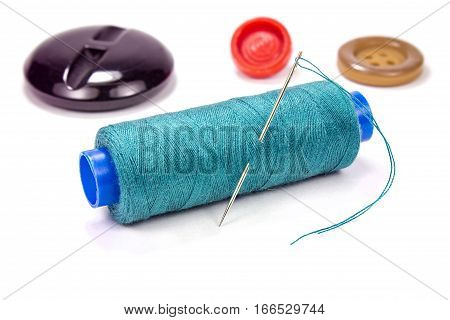 Green thread on a plastic spool with needle and buttons on white background