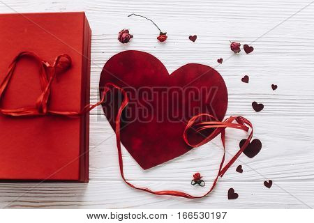 Stylish Velvet Hearts And Red Present On Rustic White Wooden Background. Happy Valentines Day Concep