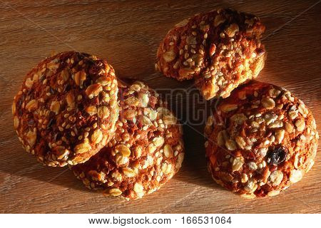 Cookies covered with nuts and raisins on a wooden board under the sunlight