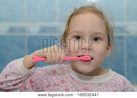 shaggy girl in pajamas brushing his teeth
