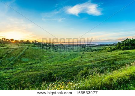 Hilly green landscape of central Russia at sunset. Gullies and ravines typical landscape of the Belgorod region.
