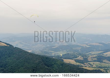 Parachute Skydiver Flying In Clouds At Top Of Mountains With Amazing View, Travel Adventure Concept,