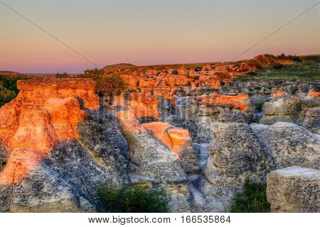 Sunrise shining over the Hoodoo badlands at Writing-on-Stone Provincial Park in Alberta Canada. The area contains the largest concentration of First Nation petroglyphs (rock carvings) and pictographs (rock paintings) on the great plains of North America.