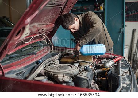 Mechanic Man Worker Pouring Antifreeze In The Cooling System