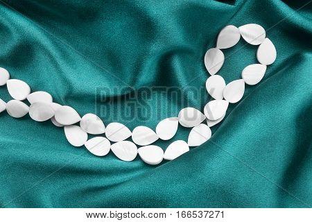 String of pearl beads on crumpled cyan silk closeup