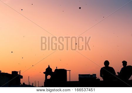 Silhouette of people flying kites at sunset in Jaipur on Makar Sankranti. The sky is filled with kites