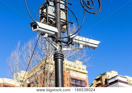 Security camera surveillance on the urban street lamppost on a background of blue sky. The color image. Big Brother is watching through lens.